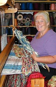 Woman weaving rag rugs at a loom.