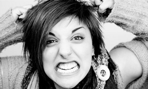 A black and white photograph of an angry young woman baring her teeth.