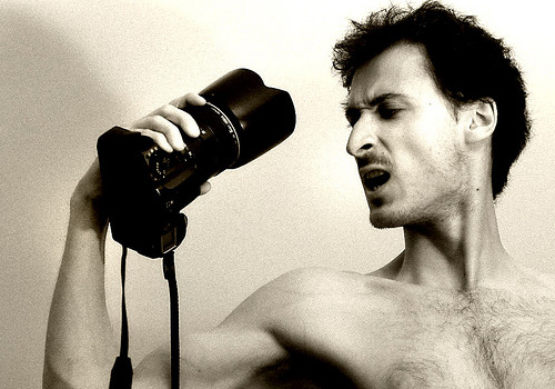 A photograph of a pale man holding an expensive camera, and snarling at it.